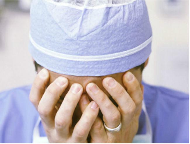 врач закрыл лицо руками