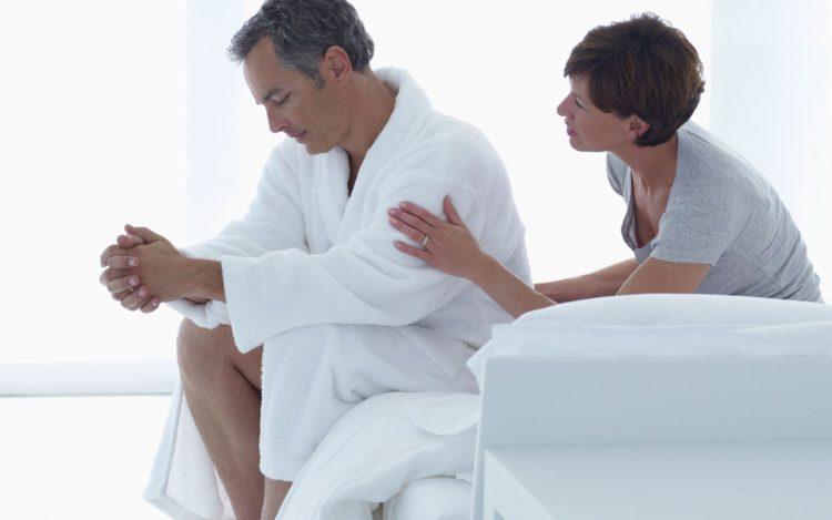 Женщина утешает мужчину на кровати