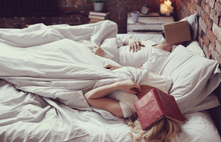 пара в постели спит с книгами на голове